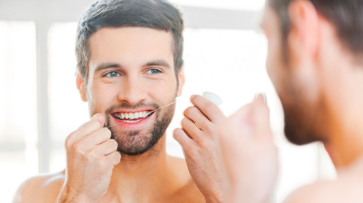 Handsome Male Flossing Teeth